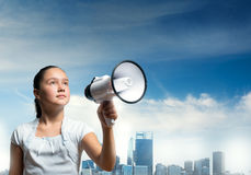 Kid with megaphone. Girl of school age with megaphone on cityscape background Royalty Free Stock Photo