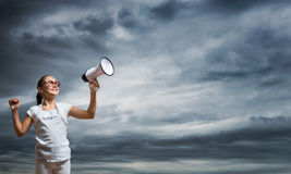 Kid with megaphone. Girl of school age with megaphone on cloud background Royalty Free Stock Photos