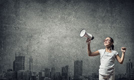 Kid with megaphone. Girl of school age with megaphone in empty concrete room Royalty Free Stock Photo