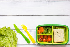 Kid menu lunchbox for school top view on wooden background Royalty Free Stock Images