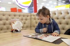 Kid with menu Royalty Free Stock Photography