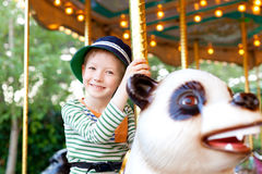 Kid at the merry-go-round Stock Images