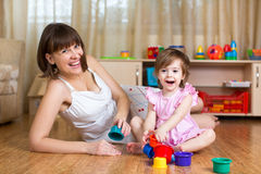 Kid and mom play at home. Kid girl and mom playing together with colorful toys Stock Photos