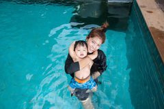 The kid and mom play together in the pool. In the condominium Royalty Free Stock Photography