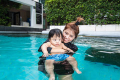 The kid and mom play together in the pool. In the condominium Stock Photos