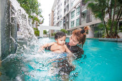 The kid and mom play together in the pool. In the condominium Stock Image