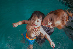 The kid and mom play together in the pool Royalty Free Stock Photos