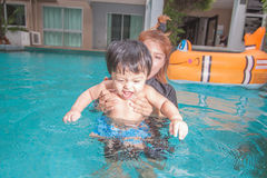 The kid and mom play together in the pool Royalty Free Stock Photography
