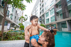 The kid and mom play together in the pool. In the condominium Stock Photography