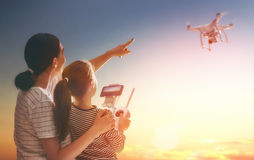 Kid and mom playing with drone. Little girl and her mother are operating the drone by remote control in the park. Kid and mom are playing with quadrocopter Royalty Free Stock Photos