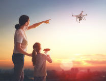 Kid and mom playing with drone. Little girl and her mother are operating the drone by remote control in the park. Kid and mom are playing with quadrocopter royalty free stock images