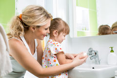 Kid with mom washing hands. Kid washing hands with mom Stock Images