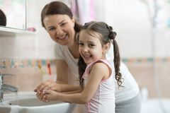 Kid with mom washing her hands in bathroom Stock Images