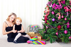 Kid and mother. Near new-year tree royalty free stock photos