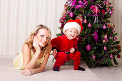 Kid and mother. Near new-year tree royalty free stock photo