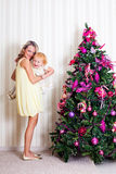 Kid and mother. Near new-year tree royalty free stock image