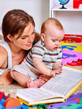 Kid with mother baby boy on floor and read book. Kid son and mother baby boy lying on floor and read book. Baby education with mother stock photography