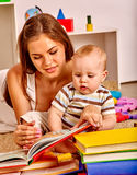 Kid with mother baby boy lying on floor and read book. Royalty Free Stock Image