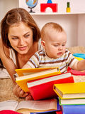 Kid and mother baby boy lying on floor and read books. Royalty Free Stock Photos