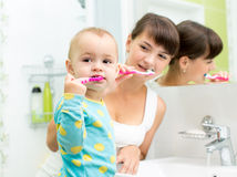 Kid and mother brushing teeth Royalty Free Stock Images
