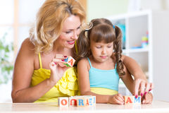 Kid and mother building the word mama playing Royalty Free Stock Photography