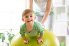 Kid and mother with fitness ball. Kid boy and mother doing exercises with fitness ball Royalty Free Stock Photo