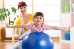 Kid and mother with fitness ball. Kid girl and mother doing exercises with fitness ball Stock Images