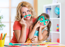 Kid with mother have a fun cutting out scissors Royalty Free Stock Photography