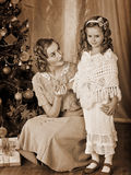 Kid with mother near Christmas tree Stock Photo