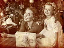 Kid with mother near Christmas tree and gifts. Stock Photos