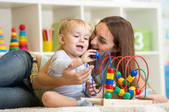 Kid and mother play with educational toy indoor Royalty Free Stock Image
