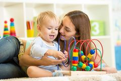 Kid and mother play with educational toy Stock Photo