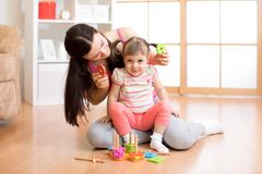 Kid and mother play together with puzzle toy. Kid and mother playing together with puzzle toy stock image