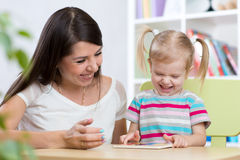 Kid and mother play together with puzzle toy Stock Images