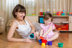Kid and mother play together with toys Stock Image