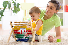 Kid and mother playing with abacus at home Royalty Free Stock Images