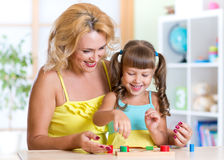 Kid and mother playing together with educational Stock Photo