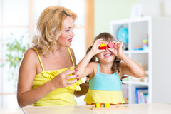 Kid and mother playing together with puzzle toy Stock Photography