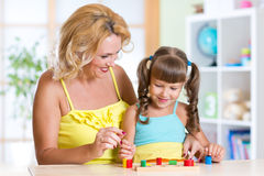 Kid with mother playing together at table Royalty Free Stock Images