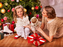 Kid with mother receiving gifts under Christmas Stock Image