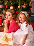 Kid with mother receiving gifts under Christmas Royalty Free Stock Image