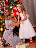 Kid with mother receiving gifts under Christmas Royalty Free Stock Photo