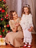 Kid with mother receiving gifts under Christmas Stock Images