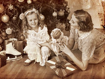 Kid with mother receiving gifts under Christmas Stock Photos