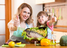 Kid and mother show thumb up cooking in kitchen Stock Images