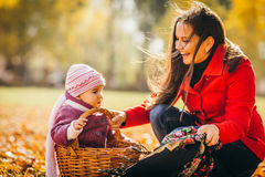 Kid and mother sit with apples basket outdoors in autumnal park Stock Photos