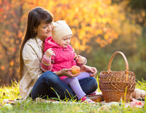 Kid and mother sit with apples basket outdoors in autumnal park Royalty Free Stock Photo