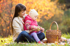 Kid and mother sit with apples basket outdoors in autumnal park Royalty Free Stock Image