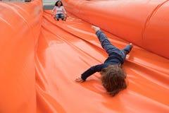 Kid slide on a giant inflatable slider stock images
