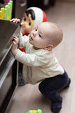Kid mounting on cupboard Royalty Free Stock Images